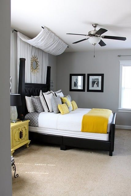 Gray, yellow, and black bedroom with curtains behind headboard