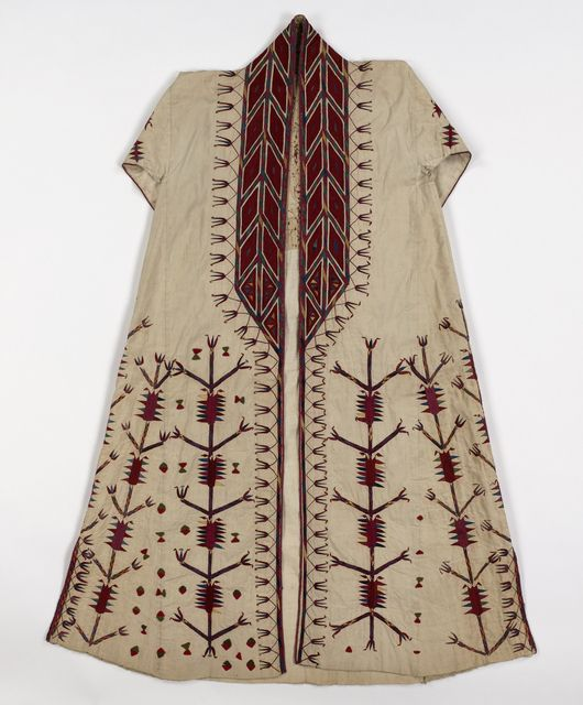 Woman's white cotton chyrpy embroidered with silk and wool felt appliqué in red, green, yellow, blue and magenta. Vertical stalks of highly stylized tulips rise from the hem, and a wide solidly-worked geometric border forms the collar and comes about half-way down the front. False sleeves fall down the back, and are joined at the wrist by a band of red cloth embroidered in black and white. The garment is lined in part with coarse white cotton cloth and is hand-sewn throughout; the lower edge…
