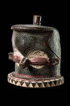 """Mask """"giphogo"""" D. R. Congo, Pende wood, mat patina, black and red paint, kaolin, helmet-shaped, expressive face with big slit eyes and a trunk-like nose, disc-shaped flattened beard with zigzag ornaments, coiffure with knob-like projection, min. dam., small missing parts, on metal base; the mask """"giphogo"""" forms part of the chief's treasure, and is kept in his residence together with other sacred objects. The masked figure represents the political leader and symbolizes ancestral power.  H: 32…"""