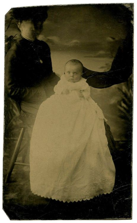 """""""Movement of the mother's head as the image was being captured has obscured her face to the point of her appearing ghostly or phantom-like. The glowing gown and the dark ribbon flowing from behind the child's head add to the mysteriousness of this photo.""""    (Source: flickr.com)"""