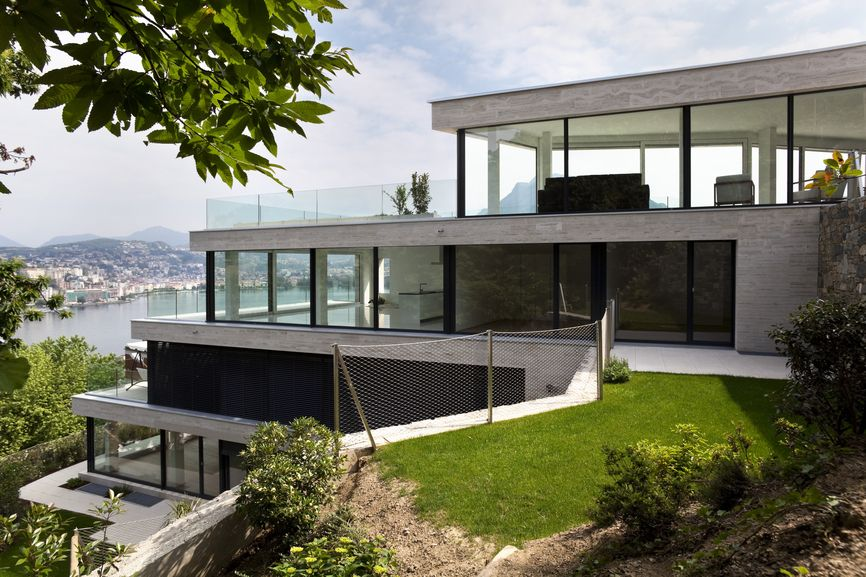 4 story white all glass modern home cascading down the slope of a steep