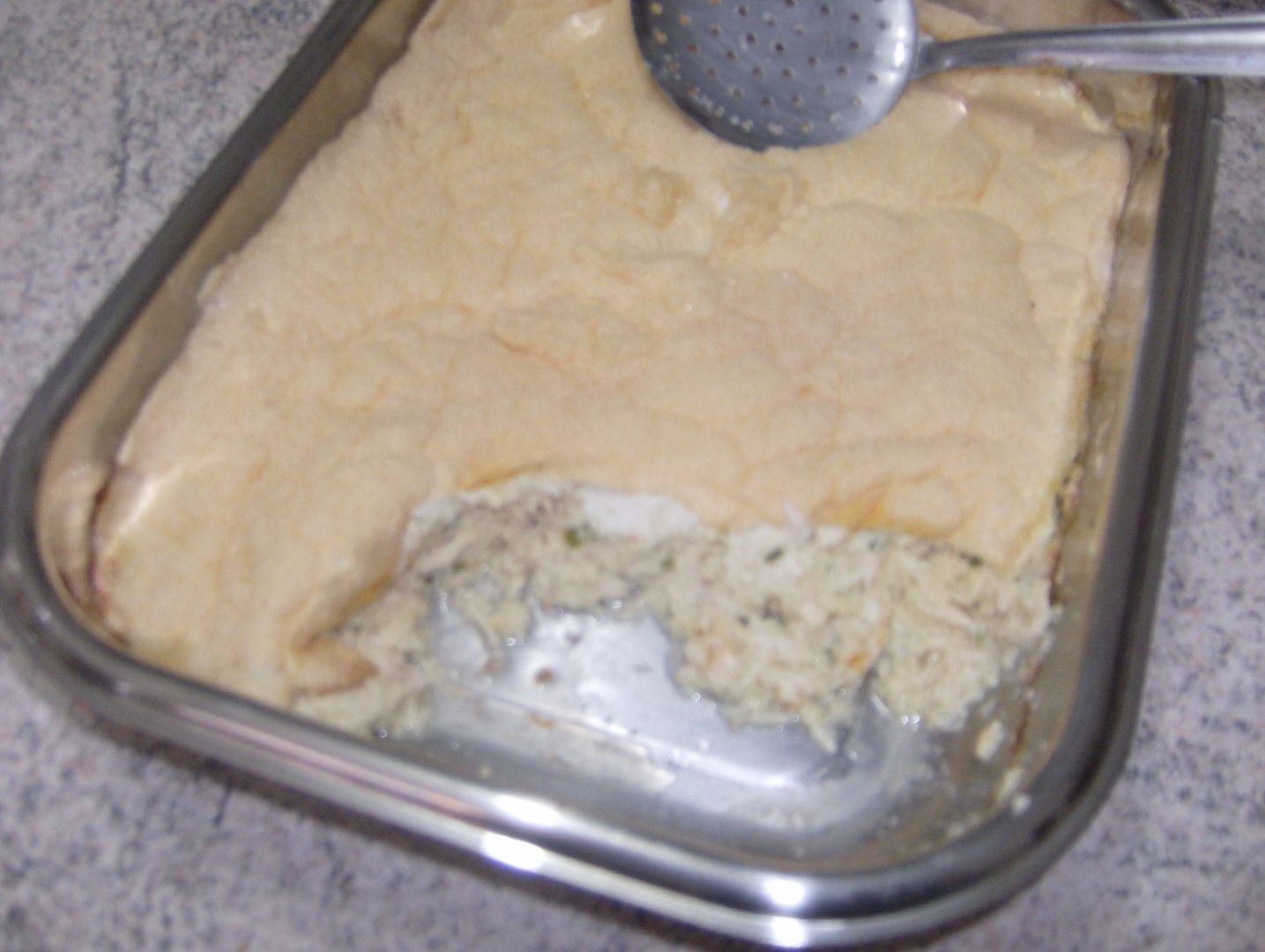 4 colheres de sopa de manteiga  - 4 colheres de sopa de farinha de trigo  - 1 cebola grande ralada  - 6 gemas  - 6 claras em neve  - 1 Kg de peito de frango cozido em tempero a gosto  - 4 xícaras de chá de caldo de galinha  - 3 xícaras de chá de leite quente  -