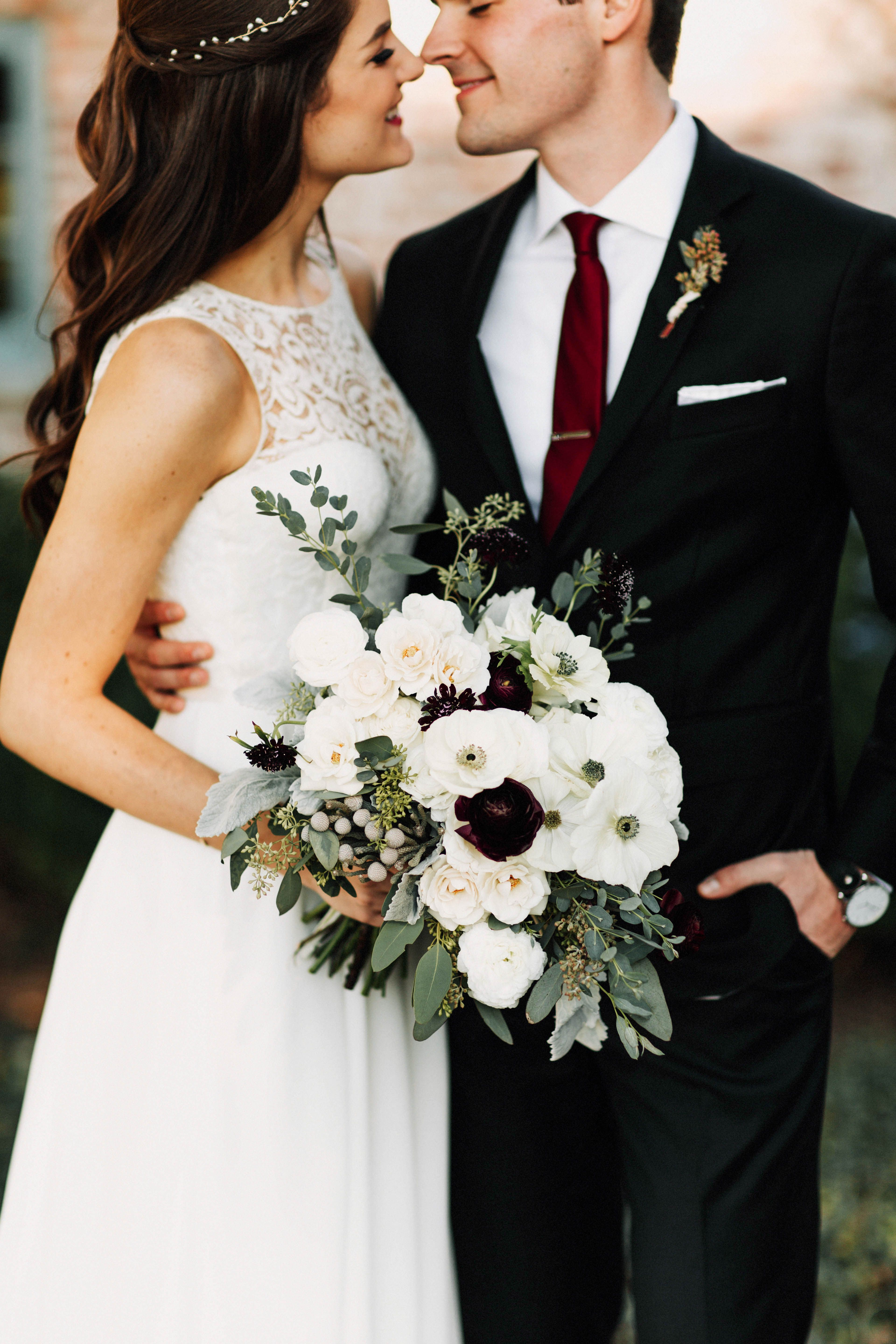 A Bride In Her Lace Gown Holds Her Loose Bridal Bouquet Of