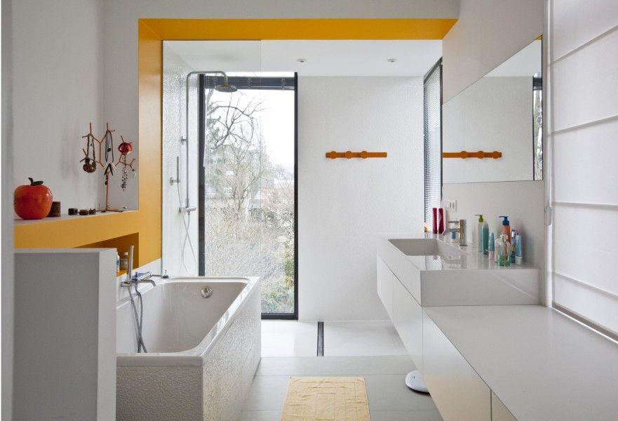 Douchen met zicht op de tuin. Een subtiele streep warm geel vrolijkt de badkamer op.