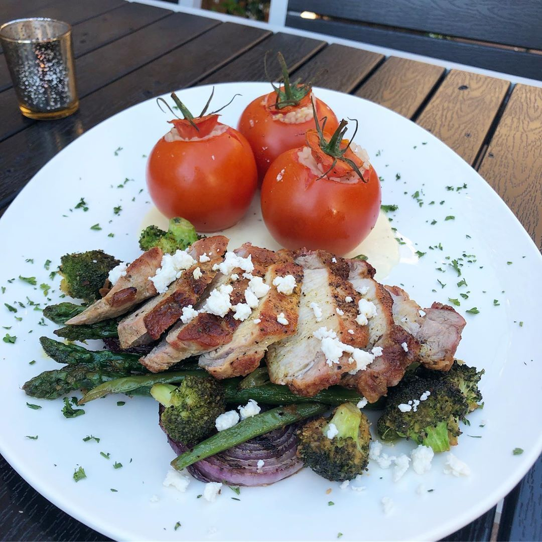 a pan seared pork chop, sliced, served over sautéed peas, asparagus, broccoli and grilled onion rings, topped with manouri cheese crumbles. We are serving this with rice stuffed tomatoes served over a cream sauce.