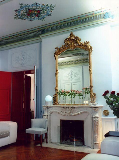 Salon haussmannien avec parquet à chevrons cheminée dépoque et miroir doré