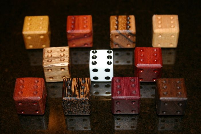 This is an image of several handcrafted dice beside a standard die for size comparison.