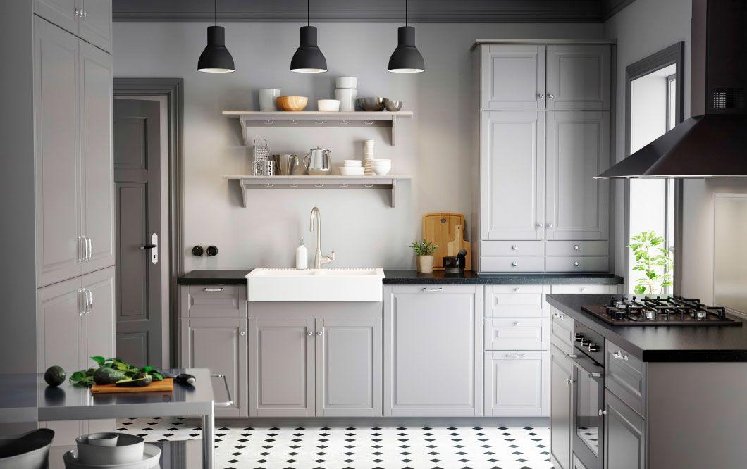 Kuchyňa vo vidieckom štýle so sivými dvierkami, čiernymi pracovnými doskami a chrómovanými úchytkami