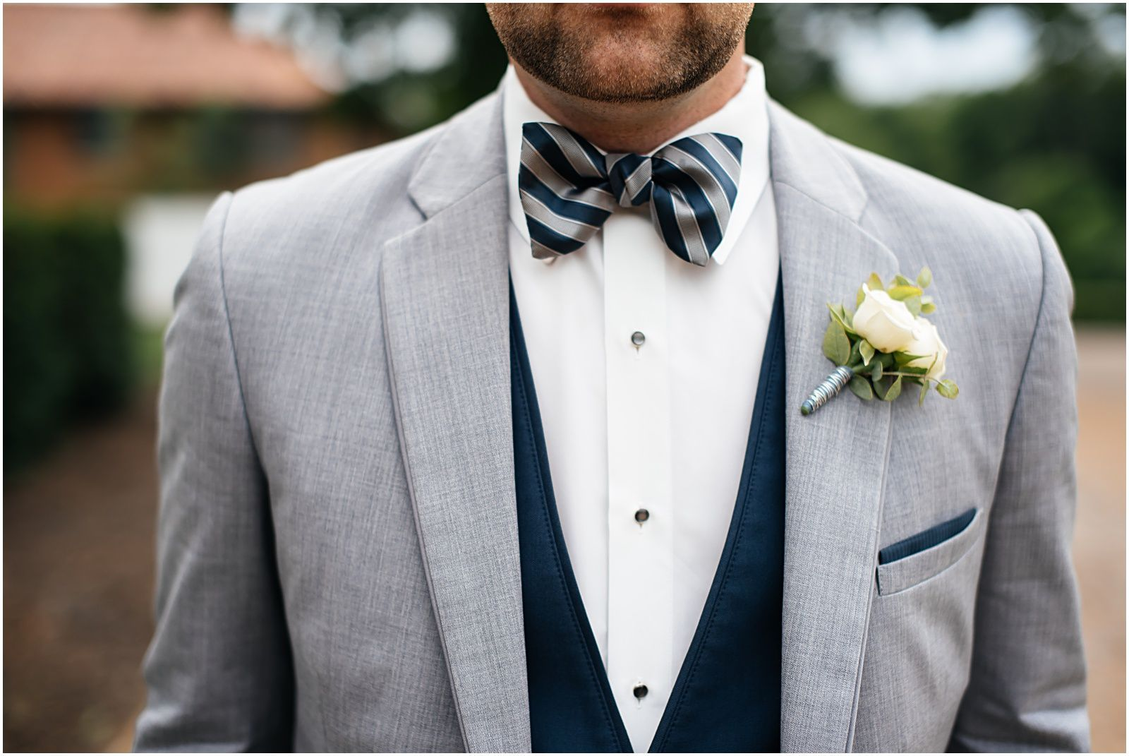 Groom in light grey suit with navy vest, navy and grey striped bow ...