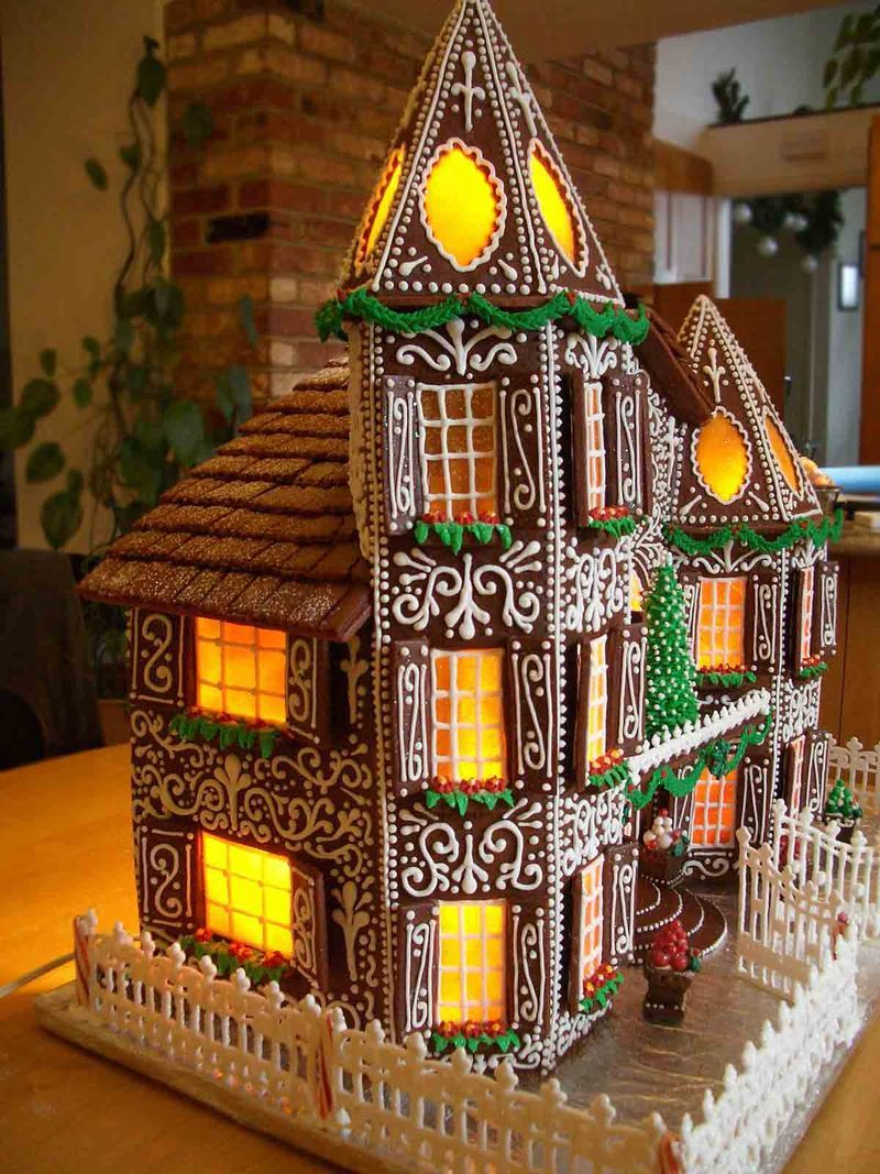 Gingerbread House 2015- Gingerbread shingles. Piped royal icing fences and gate. Butterscotch candy windows. Royal icing flowers and leaves for flower boxes. Rolled fondant evergreen swags.