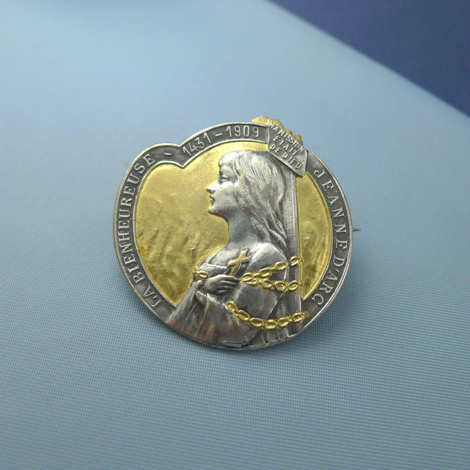 """Brooch of La Bienheureuse Jeanne d'Arc, 1431-1909 [beatification], """"Ma Mission était de Dieu."""" Silver-plated brass, front. (US $187)"""