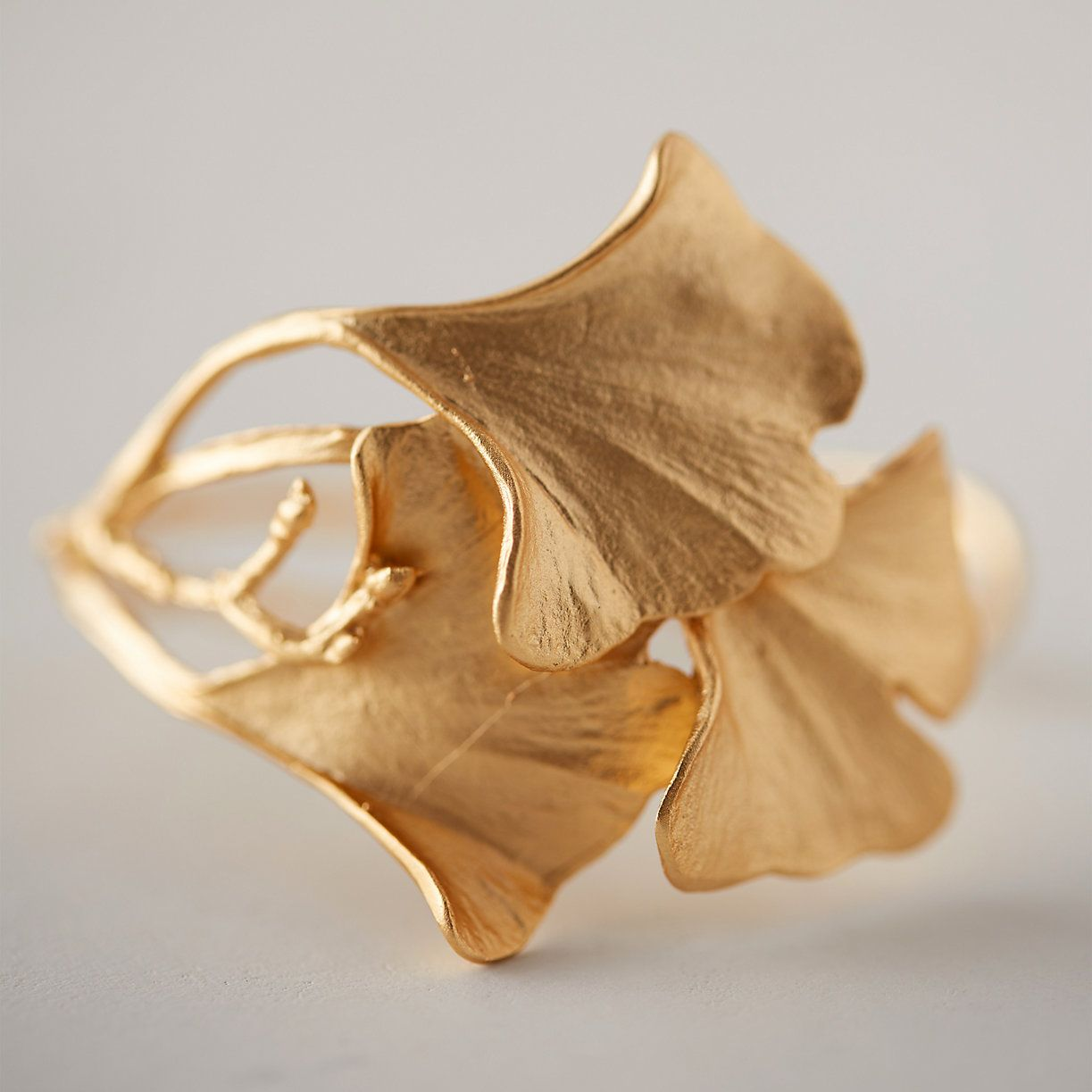 """Hand-cast in a mold created directly from overlapping gingko leaves, this graceful cuff was crafted by New York designer Michael Michaud.- Bronze- Adjustable- Clean with soap and water as needed- Handmade in the USA2""""W, 2.25"""" diameter"""