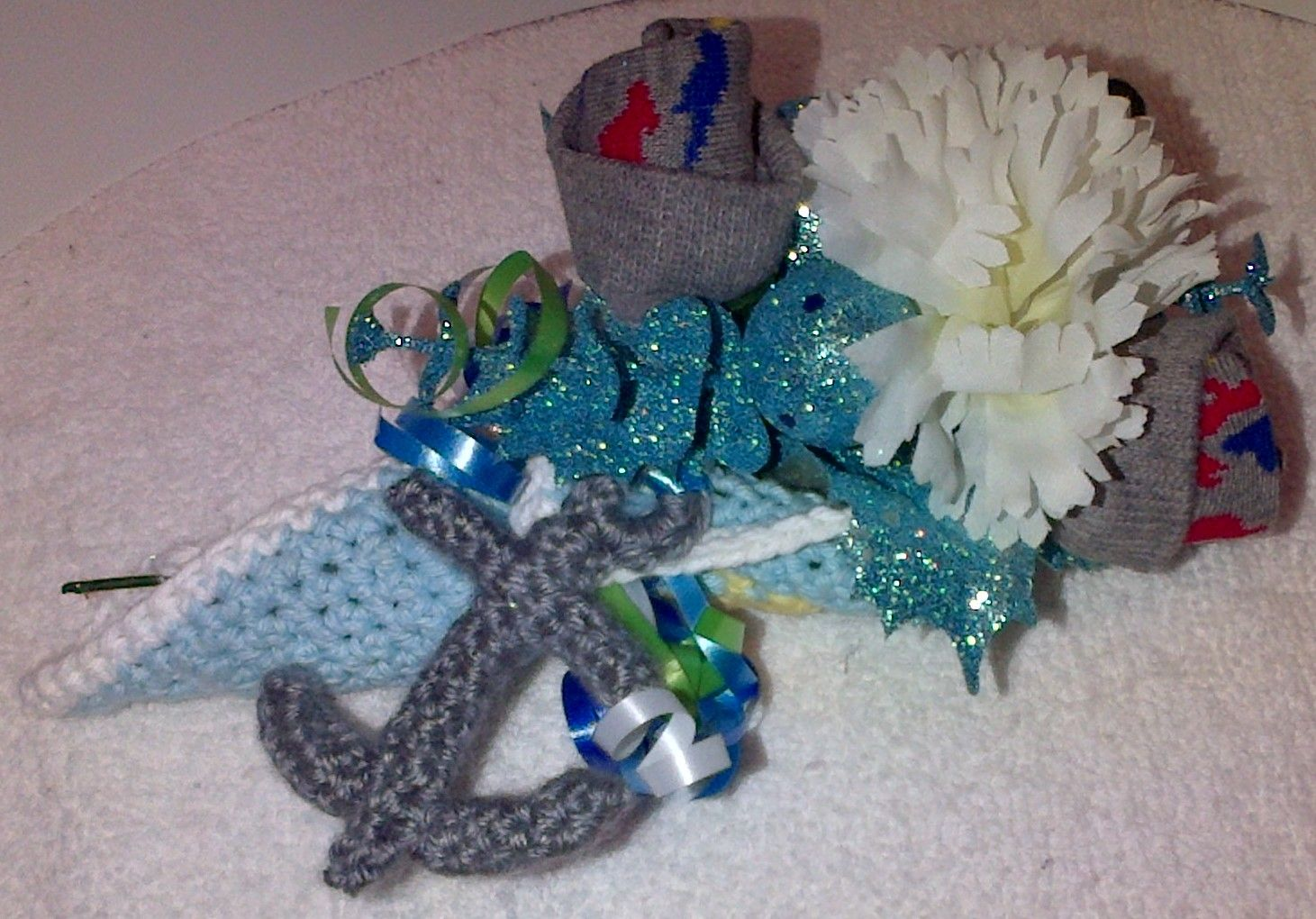 Baby Sock Corsage using a Anchor Washcloth I did for my Daughter-n-law who is having a Baby Shower on Nov.14,2015. This could also be used as a flat table decoration.