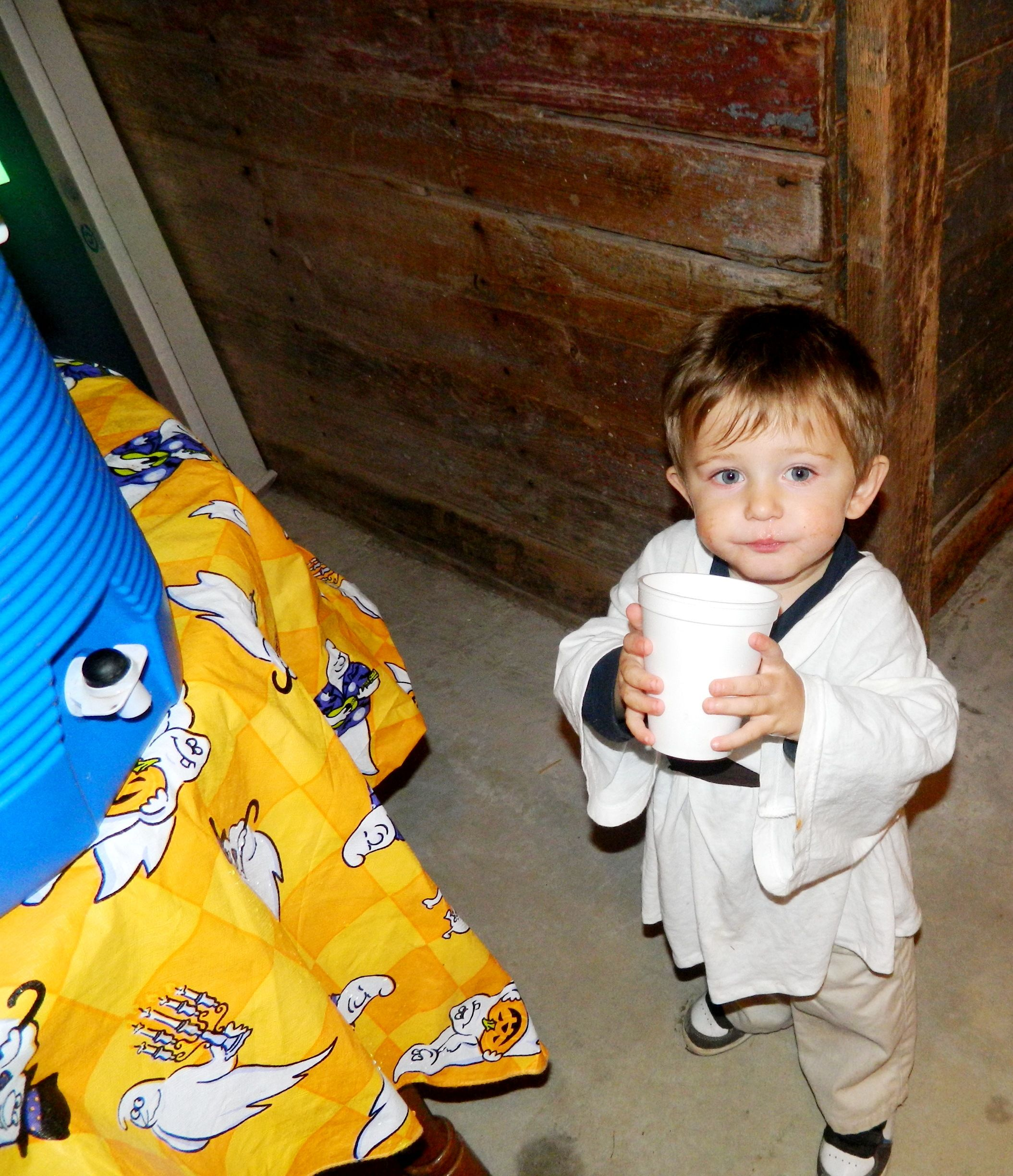 Young guest at church Halloween party enjoys his drink in the ...