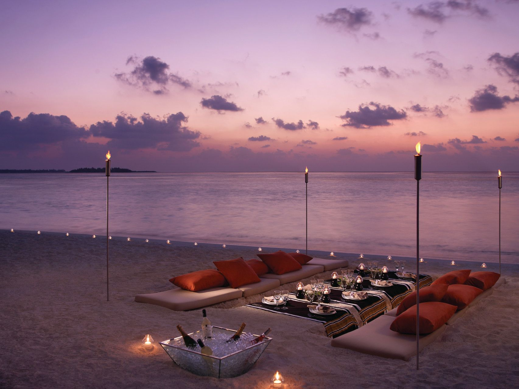 Dine al fresco on pristine sands, with lagoon and ocean views that stretch into the distance ...