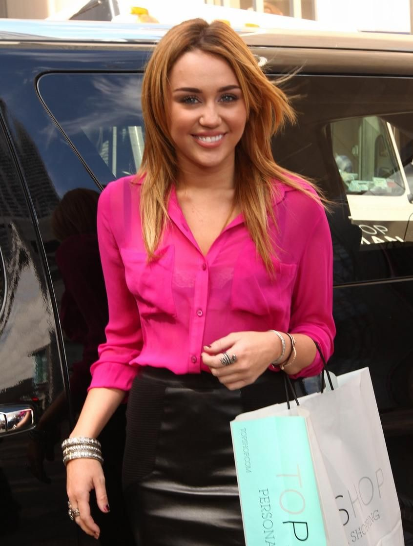 pink blouse + leather skirt. Miley and I have the same top ...