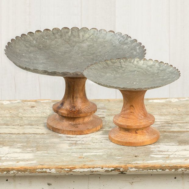 We adore this Wood Base Scalloped Metal Riser 11 Inch and we think you will love it as well. The base of this display stand is made of wood and the top of this piece is made of metal creating a country chic juxtaposition. At almost a foot in height this metal riser will add a little extra dimension to your decorative vignette.