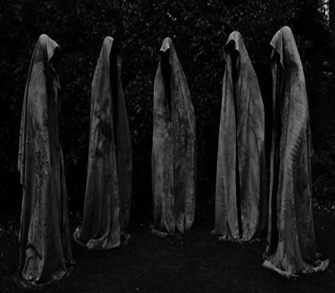 cloaked figures walking toward Cain and Lizzie...