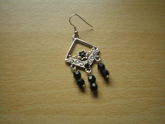 Bincos em metal prateado motivo floral e pérolas pretas.