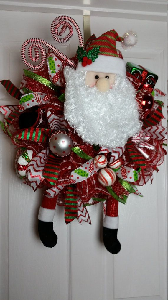 This wreath features a Santa head, legs, and hands. It has a faux present, ornaments, decorative candy, floral picks, and wired ribbon. It is red, white, and green.  W 17 L 23 with legs