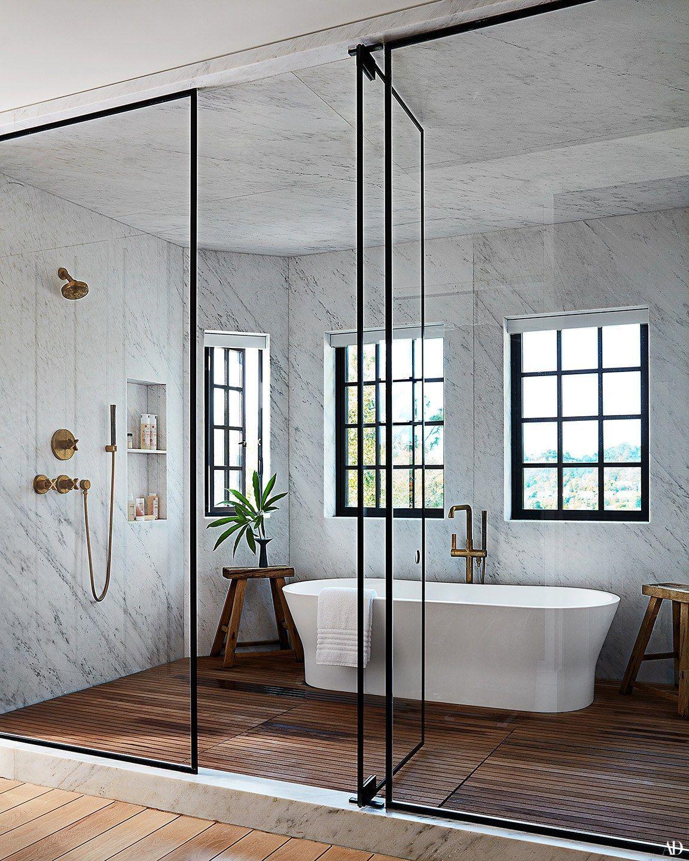 Photo of Marmor und Holz Naturbad. Badewanne im Duschbereich, Glas und Metall Duschtür. Schritt innerhalb