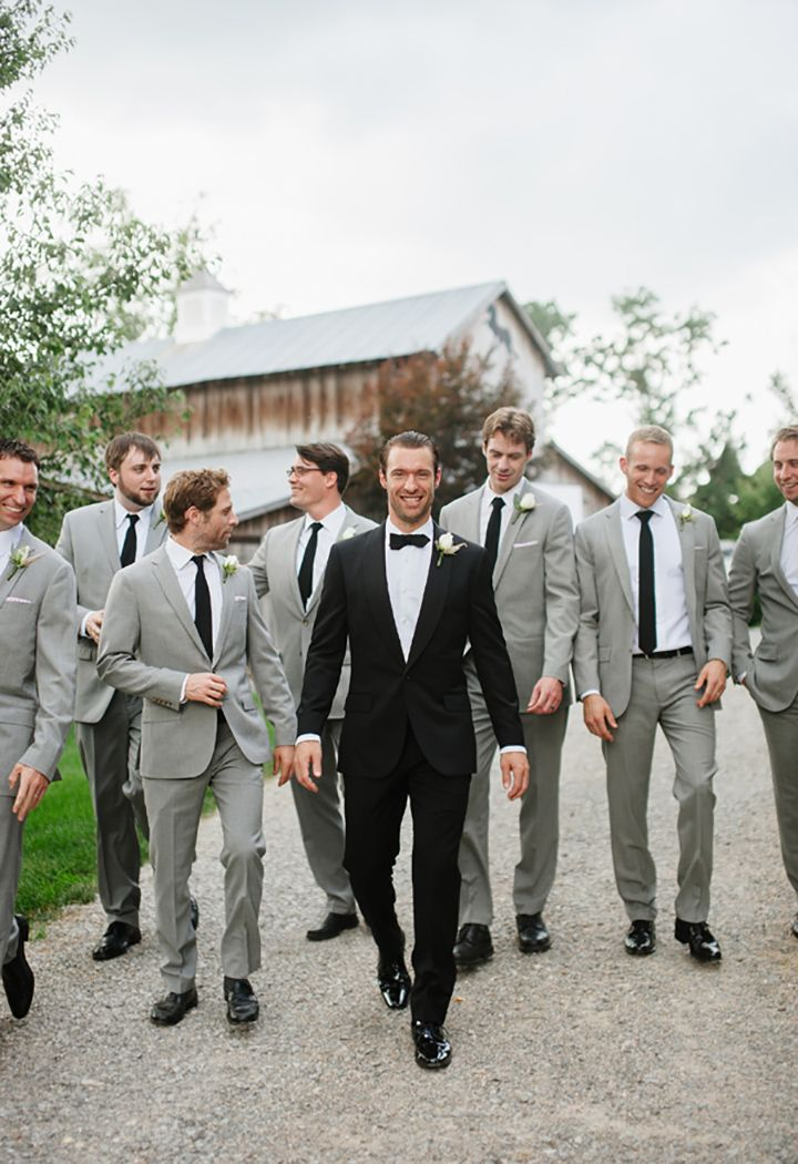 The Groom Looks Der In His Black Tux And Bow Tie With Groomsmen Light Gray Suits Ties We This Moncheribridals
