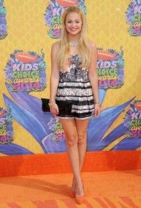 "Disney star Olivia Holt wore a stylish romper paired with HMB's ""Best shoes"" of the day (Chelsea Paris ""Jasmine"" heels in exclusive orange) to the 2014 Nickelodeon Kid's Choice Awards."