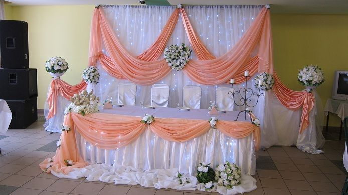 White pipe and drape backdrop with cool white fairy lights and peach satin swags. Matching head table Décor                                                                                                                                                                                 Más