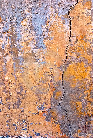 An old stained wall with major cracks and chipped paint.
