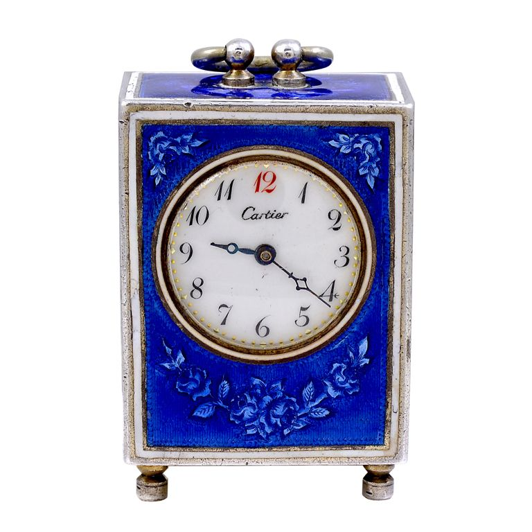 Beautiful miniature sterling silver and enamel desk timepiece by Cartier. Lovely colbalt blue enamel decorated on front, top and sides, with flowers, bows and leaves. Original dial. Clock is set on 4 tiny feet.
