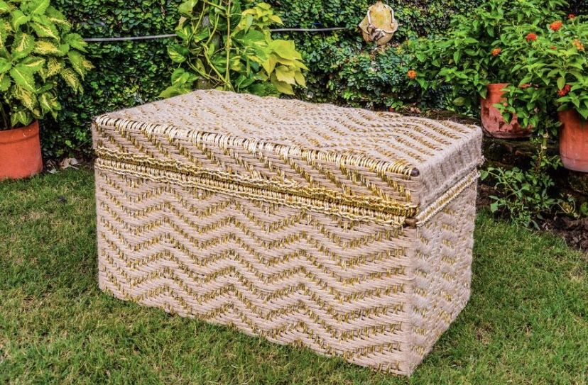 A storage box made from upcycled gold plastic wrappers and natural jute woven by our artisan women. The traditional gold design makes it the perfect wedding accessory to store clothes, jewellery, etc. #wastetowow #wovenfurniture #vintagefurniture #charpoy #charpai #weaversofinstagram #sustainableliving #sustainabledesign #circulareconomy #circularfurniture #supportyourladies #surviveandthrive #sustainableliving #sustainablefurniture #circularfurniture #skilledsamaritan #vocalforlocal #womenentre
