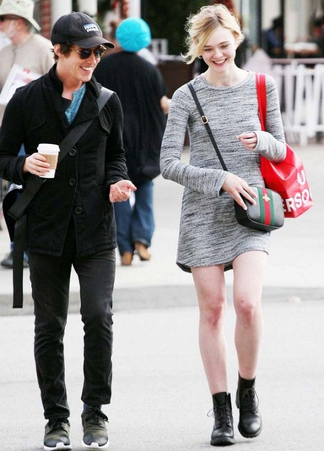 Elle Fanning wears a crewneck sweater dress, Gucci crossbody bag, and Timberland lace-up combat boots