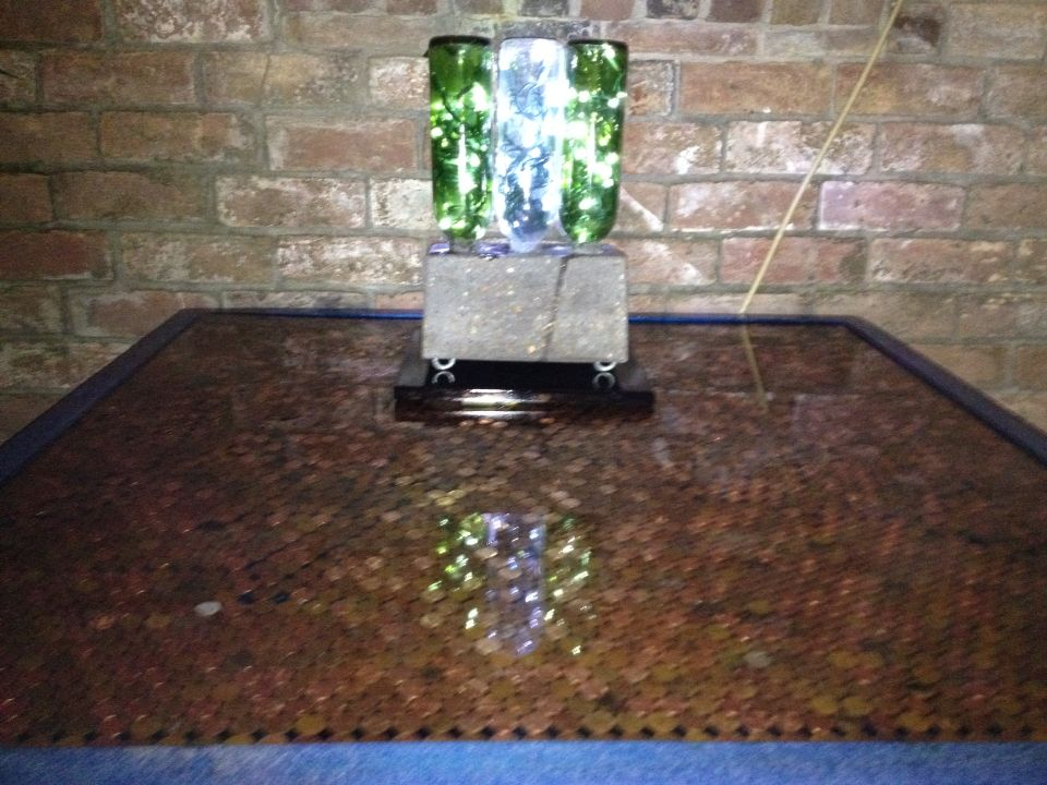 Penny table with LED wine bottles in concrete.