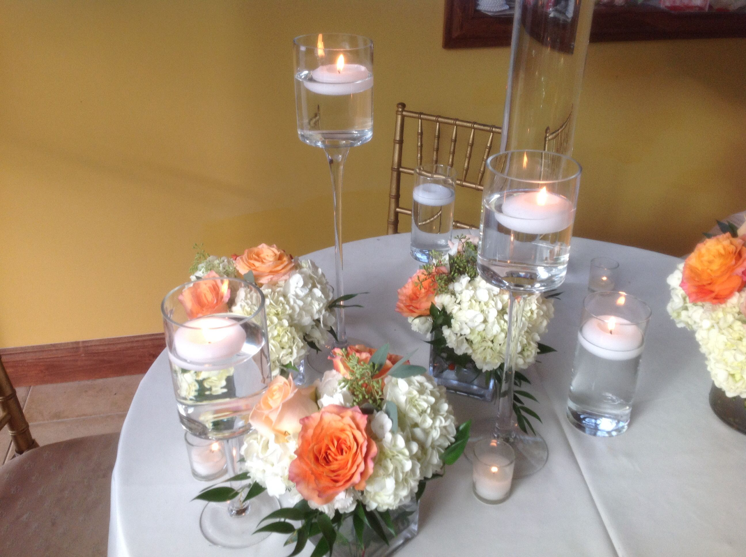 Centerpiece of white hydrangea, peach roses and Free Spirit roses in a glass cylinder.  Doristhefloristt.com