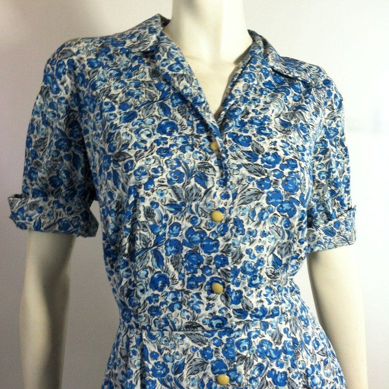 """Blue and white floral printjerseynylon 1960s dress by Casual Maker. Buttons up front, cuffed short sleeves. No flaws.Measures40"""" around bust, 30"""" around waist, 54"""" hips, 16"""" bodice, 43"""" long"""