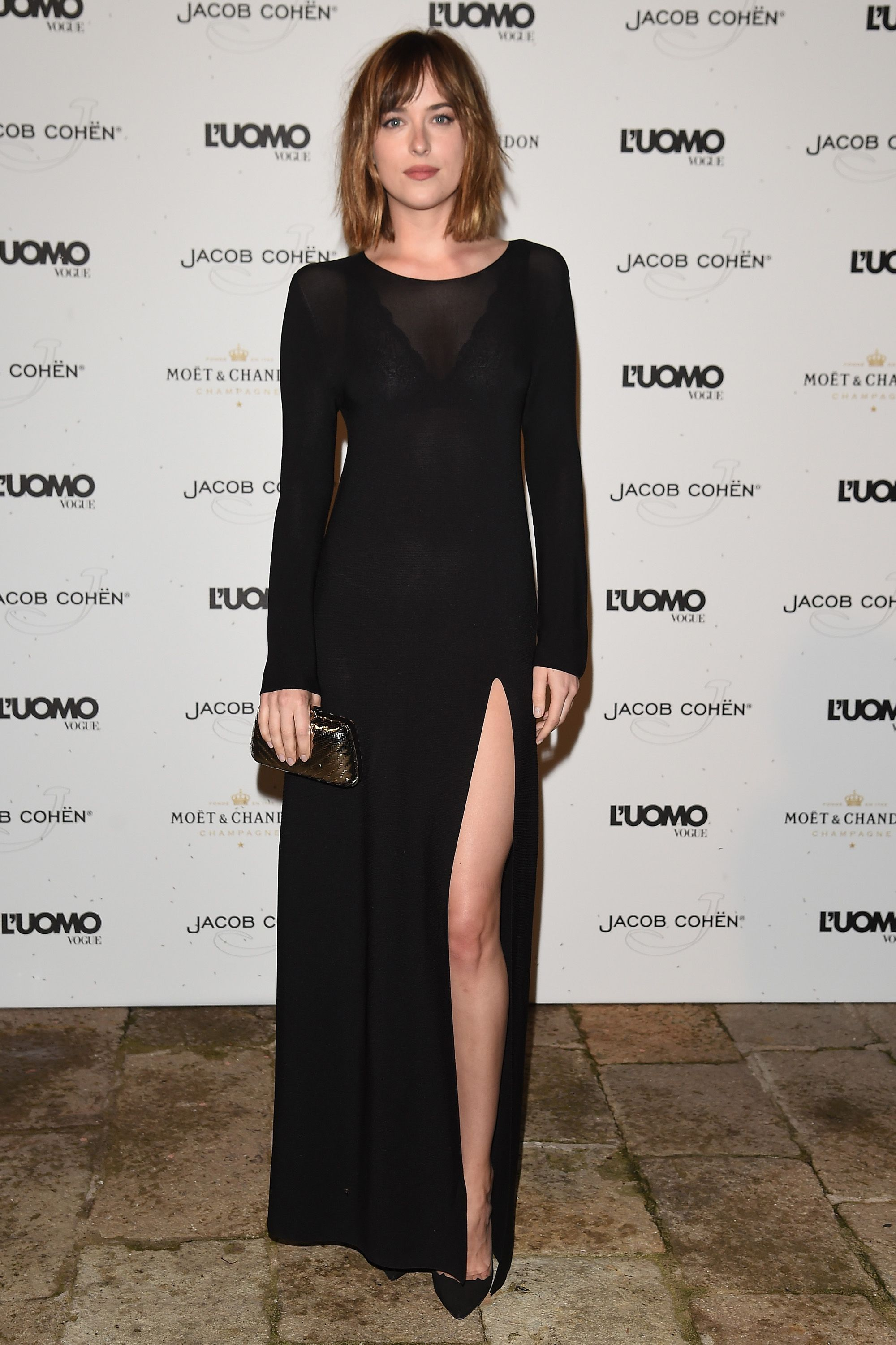 In a long-sleeved black dress with thigh-high slit - MarieClaire.com