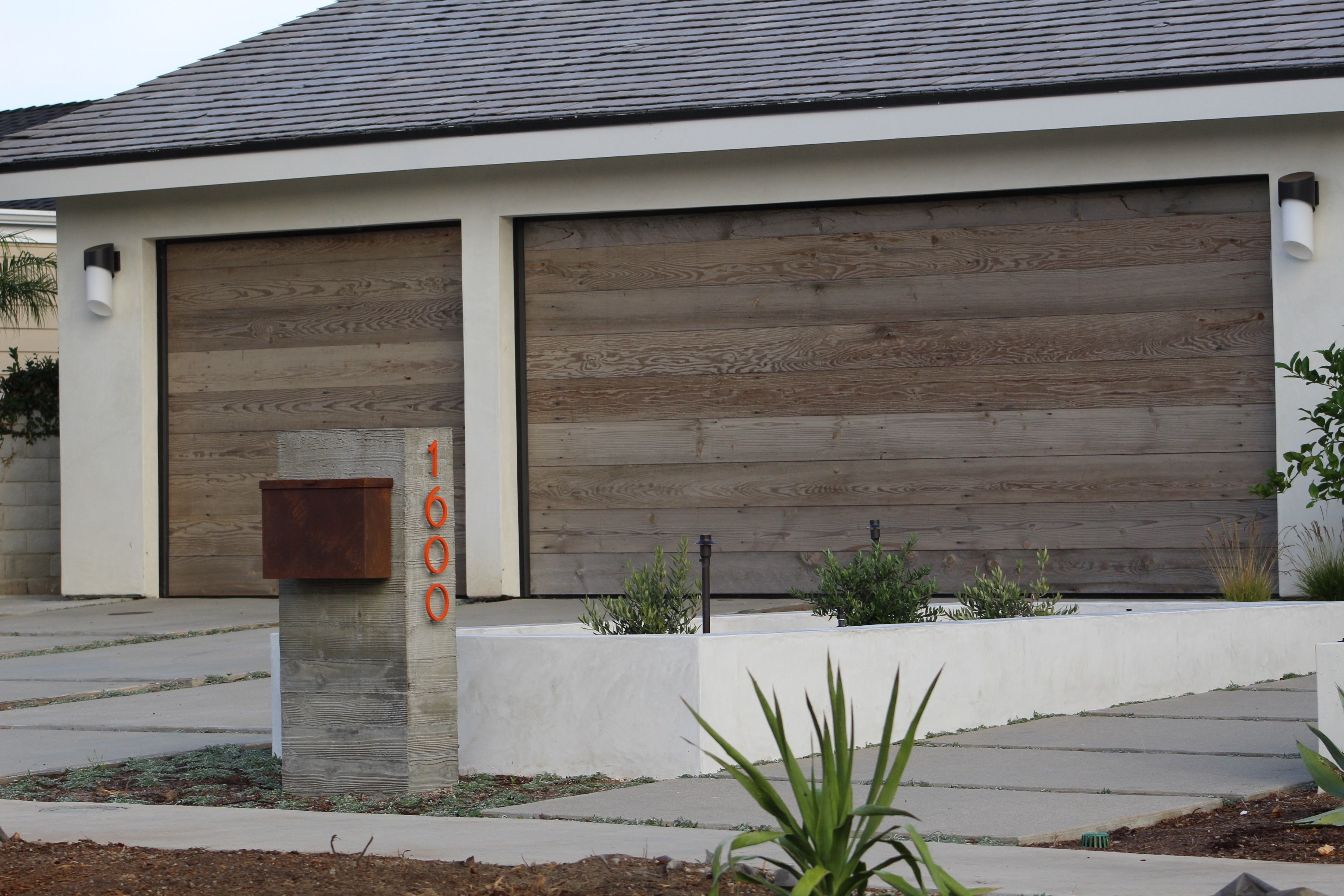 Reclaimed Wood Is A Great Alternative To Standard Garage Doors This Naturally Distressed And Weat Modern Garage Doors Wood Garage Doors Rustic Houses Exterior