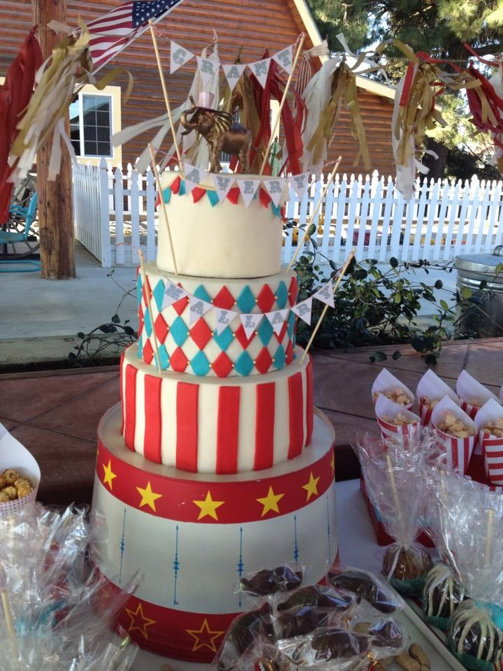 Tiered circus cake on top of painted ringmaster stand.