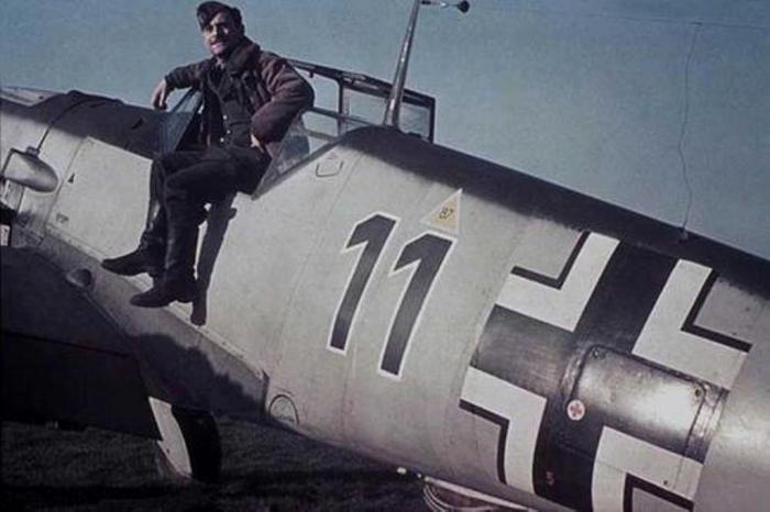 """Maldegen (Belgio). Il maresciallo Giuseppe Ruzzin seduto sul bordo della cabina di pilotaggio del Messerschmitt Me.109F """"11 nero""""."""