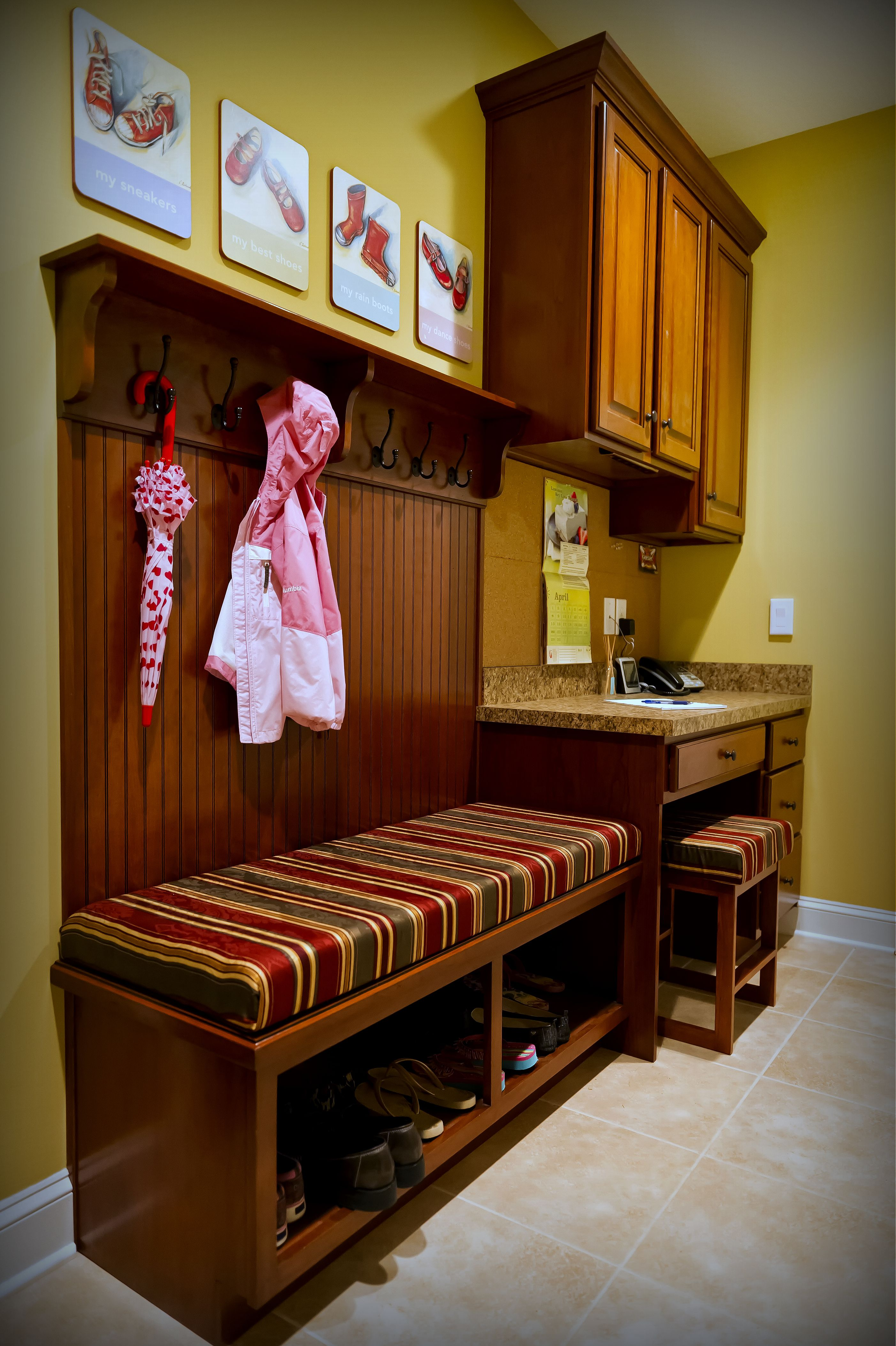 This is a custom Cherry mudroom area with a small desk and boot