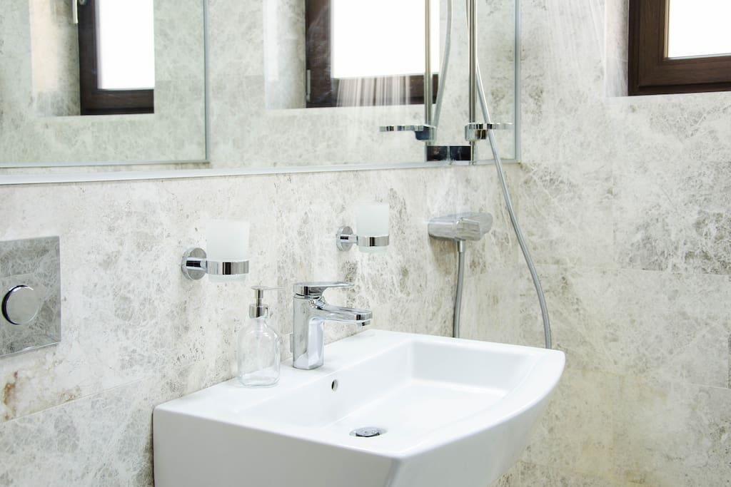 Badezimmer mit marmorierten Fliesen und morderem Waschbecken
