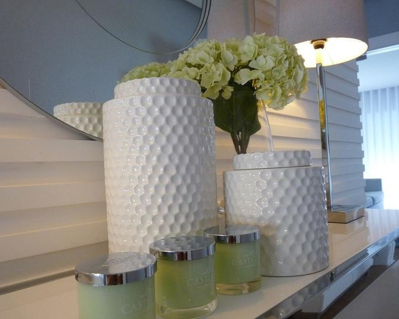 lovely textures - wall, mirror, metal table edge and lamp plant and jars.  Great job.