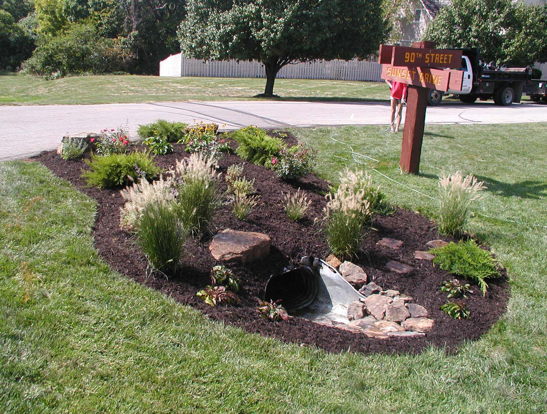 Add a garden area with water loving plants to hide an for Drain pipe landscaping