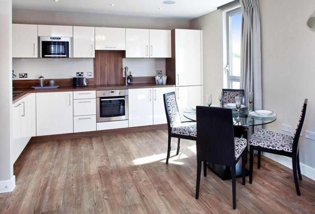 Photo Of Open Plan Beige White Veneer Kitchen With Fitted Kitchen Hardwood  Flooring Wood Flooring Upholstery