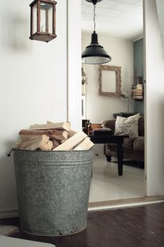 Tall Zinc Container Is Perfect As A Firewood Storage Container In A Rustic Setting Firewood Storage Indoor Firewood Storage Farm House Living Room