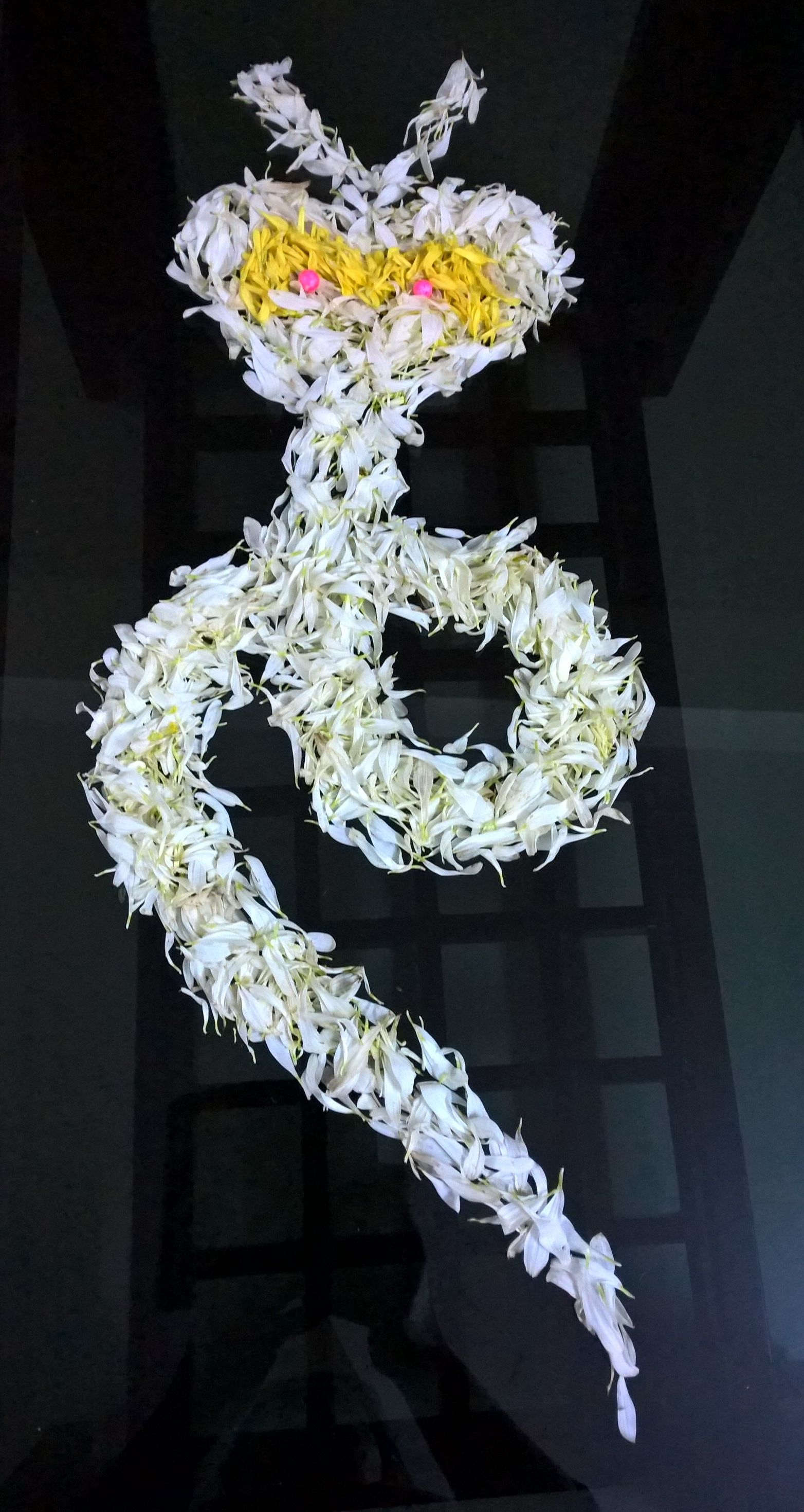 Snake 🐍 design made of white flower petals... Rangoli