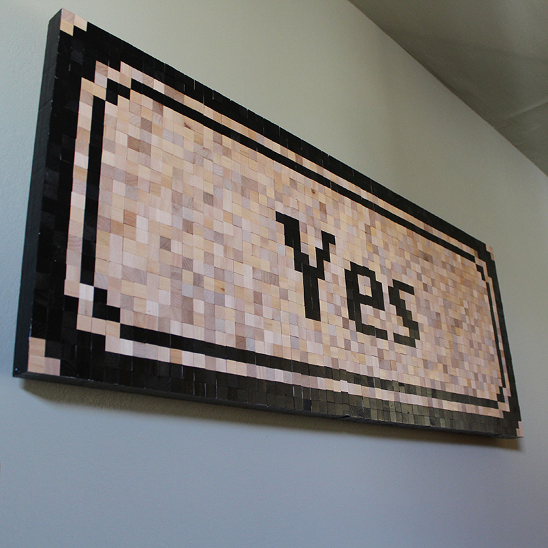 Old Mac OS Yes button recreated in thousands of wood blocks. Positive!