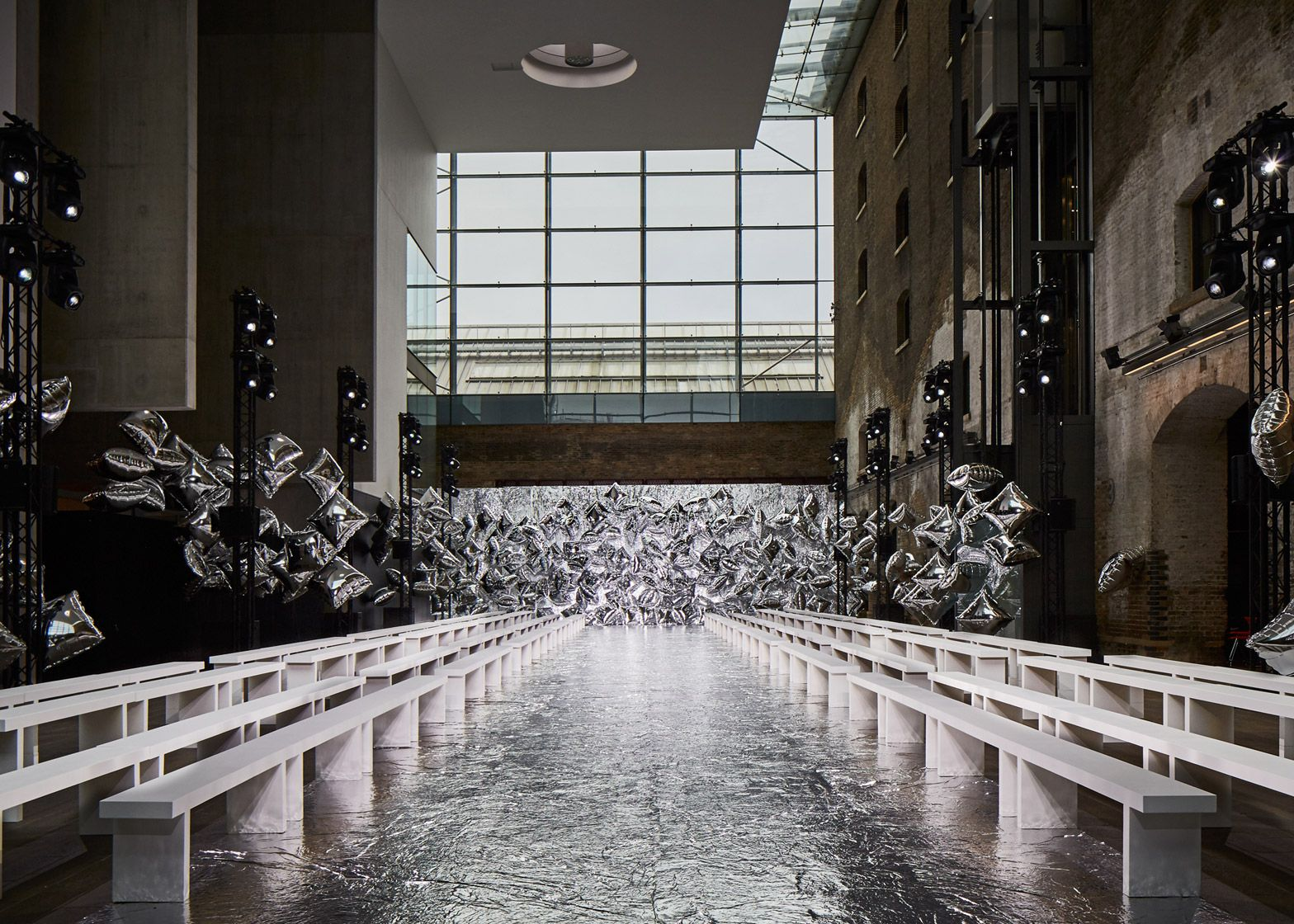 Bureau betak uses silver balloons as backdrop for mary - Fashion show stage design architecture plans ...