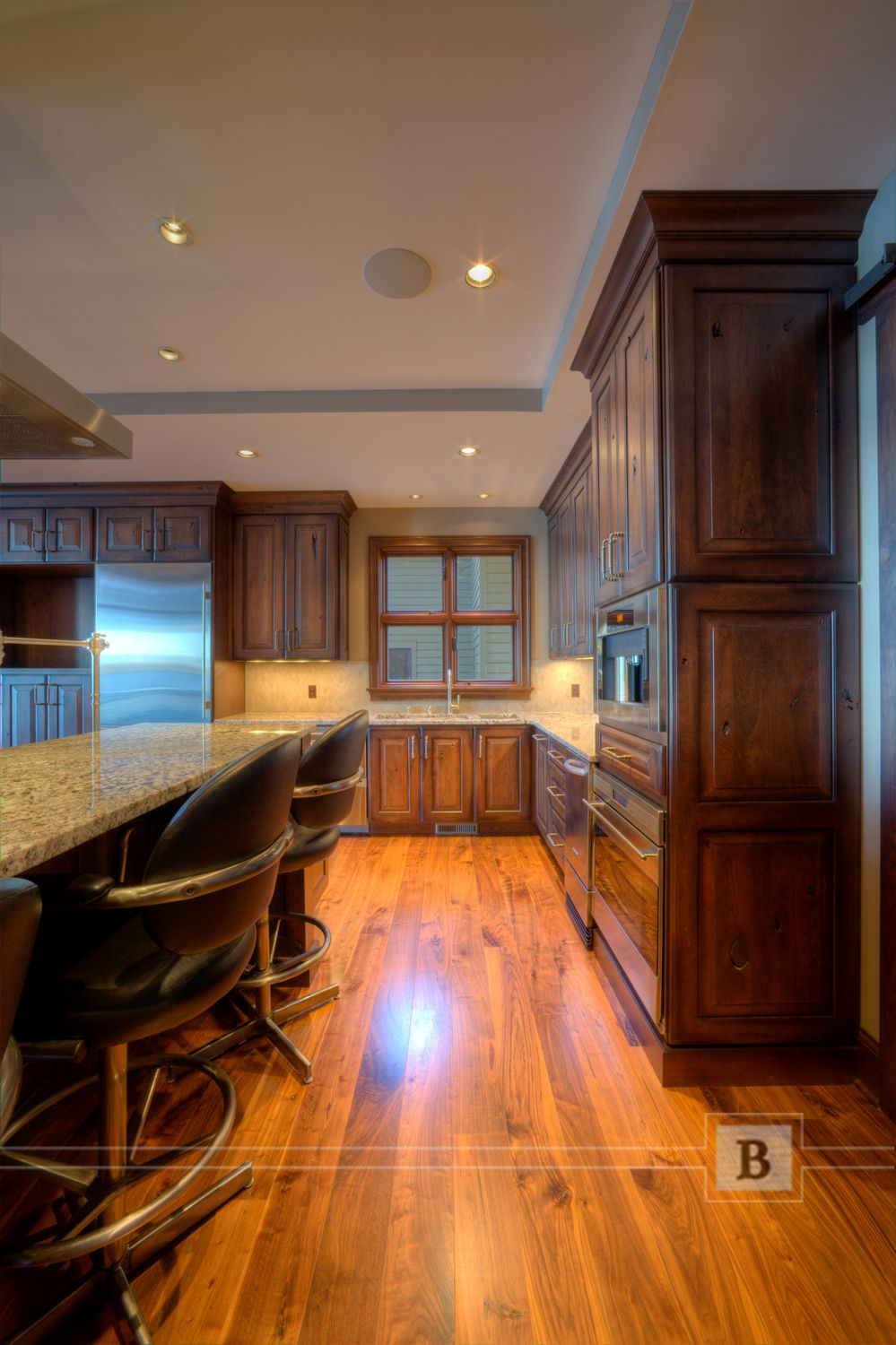 Traditional cabinetry in medium wood tones. Wood flooring and stainless steel appliances.