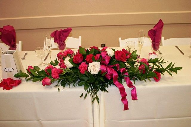 A Traditional Head Table Features A Long Low Flower Arrangement In